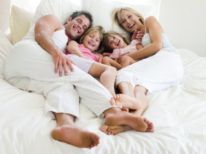 Familia que miente en la sonrisa de la cama imagen de archivo