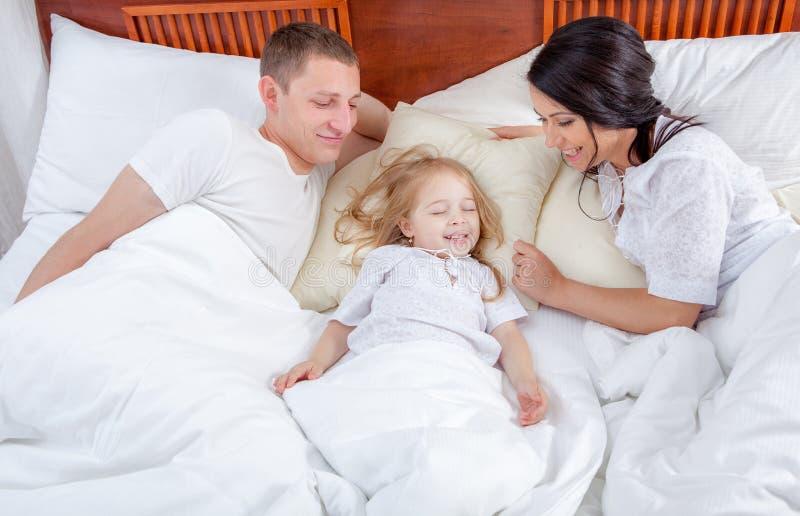 Familia que miente en una cama junto en dormitorio imágenes de archivo libres de regalías