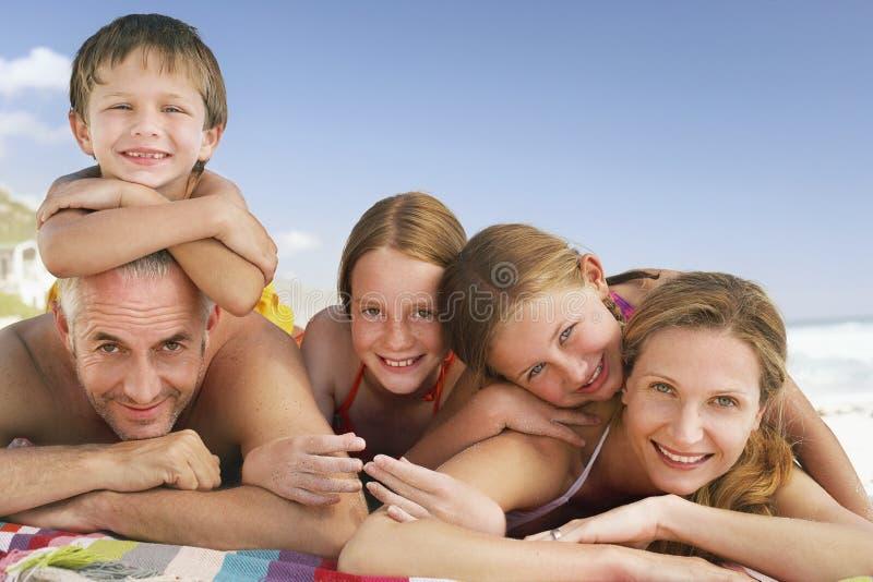 Familia que miente junto en la playa contra el cielo azul imagenes de archivo