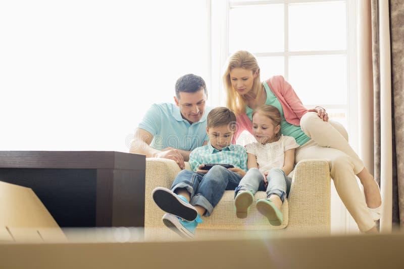 Familia que mira al muchacho que juega al videojuego de mano en casa imagen de archivo