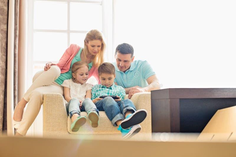 Familia que mira al muchacho que juega al videojuego de mano en casa fotografía de archivo libre de regalías