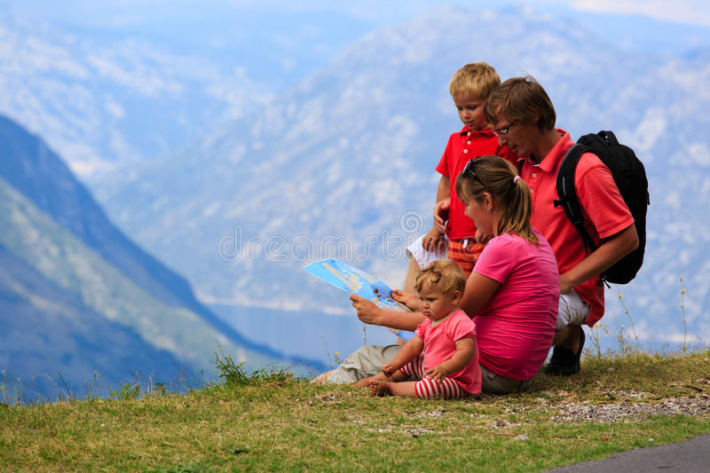 Familia que mira el mapa en montañas imágenes de archivo libres de regalías