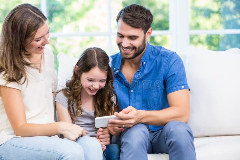 Familia que mira el teléfono elegante mientras que se sienta en el sofá foto de archivo libre de regalías