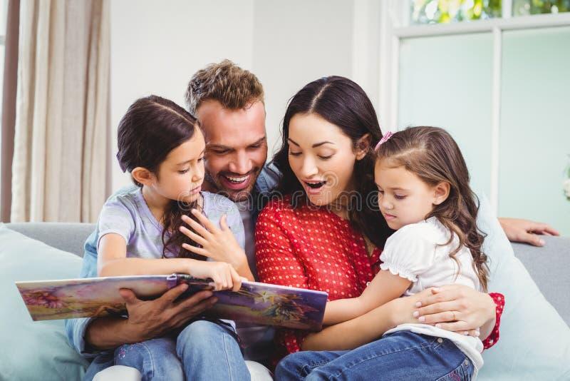 Familia que mira en libro ilustrado mientras que se sienta en el sofá fotos de archivo libres de regalías