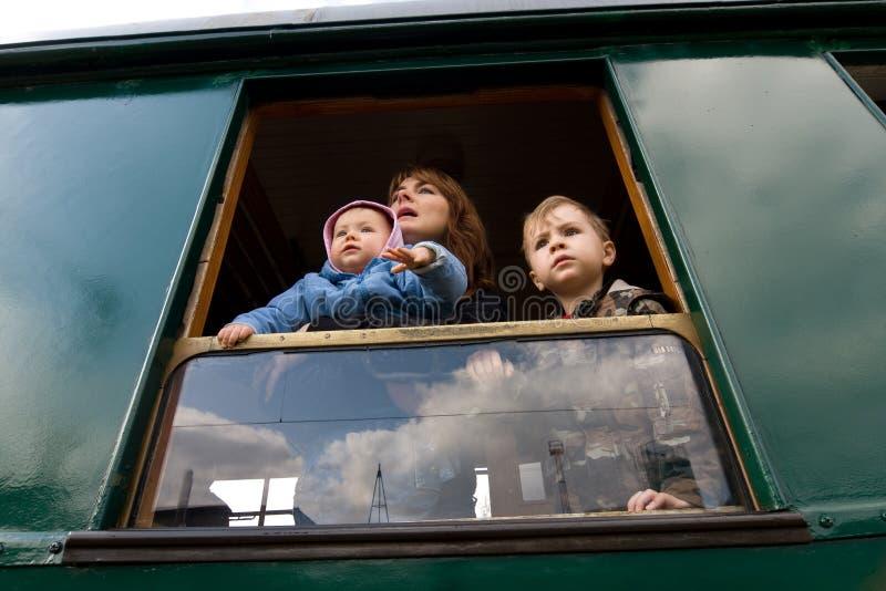 Familia que mira fuera de ventana foto de archivo
