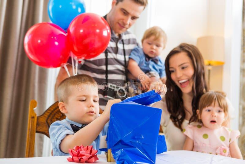 Familia que mira la caja de regalo de la abertura del muchacho del cumpleaños fotos de archivo libres de regalías