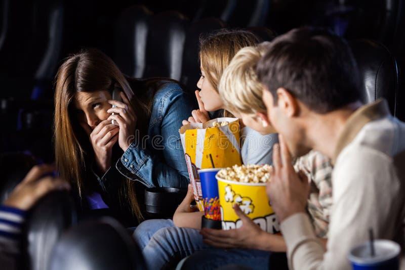 Familia que mira a la mujer que usa el móvil adentro foto de archivo libre de regalías