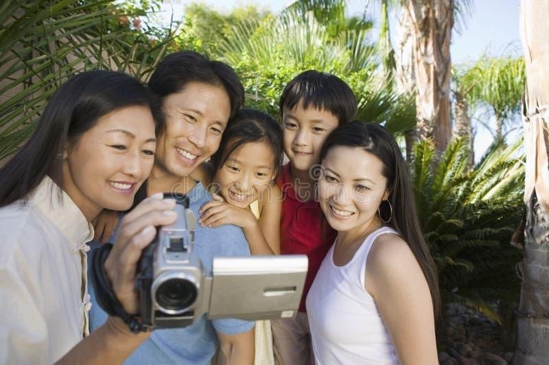Familia que mira la pantalla de la cámara de vídeo en vista delantera del patio trasero imagen de archivo