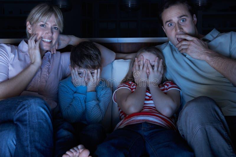 Familia que mira programa asustadizo sobre la TV imagen de archivo