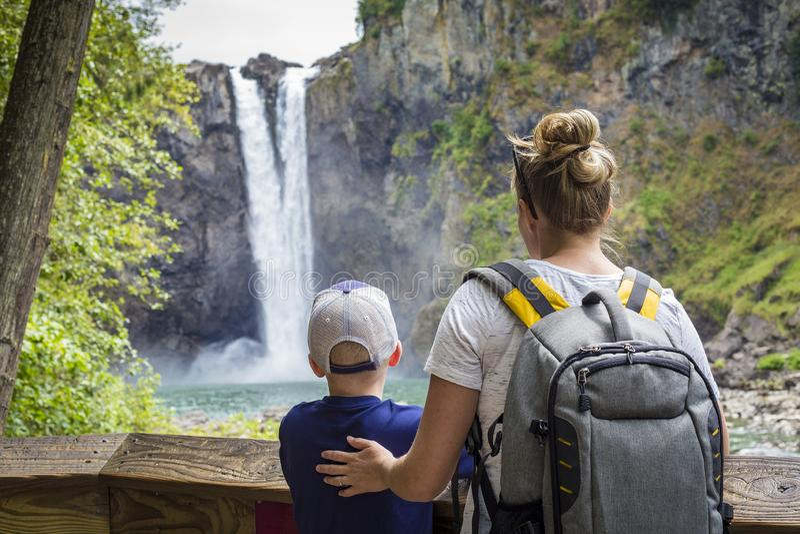 Familia que mira una cascada escénica en un alza junto imagen de archivo