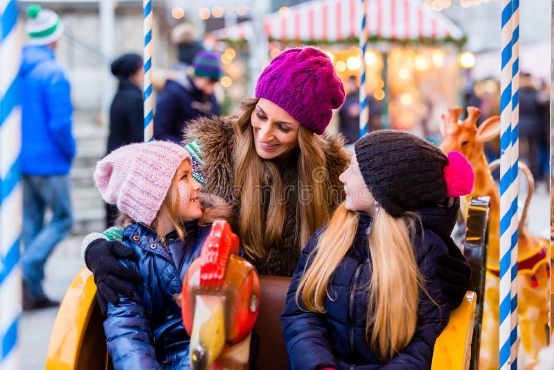 Familia que monta el carrusel en mercado de la Navidad fotos de archivo