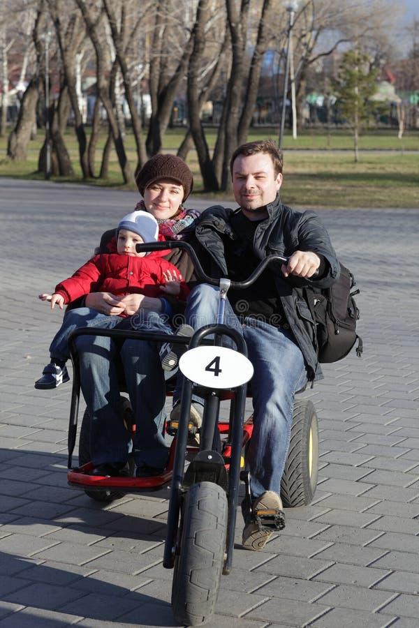 Familia que monta una bicicleta rodada tres fotografía de archivo