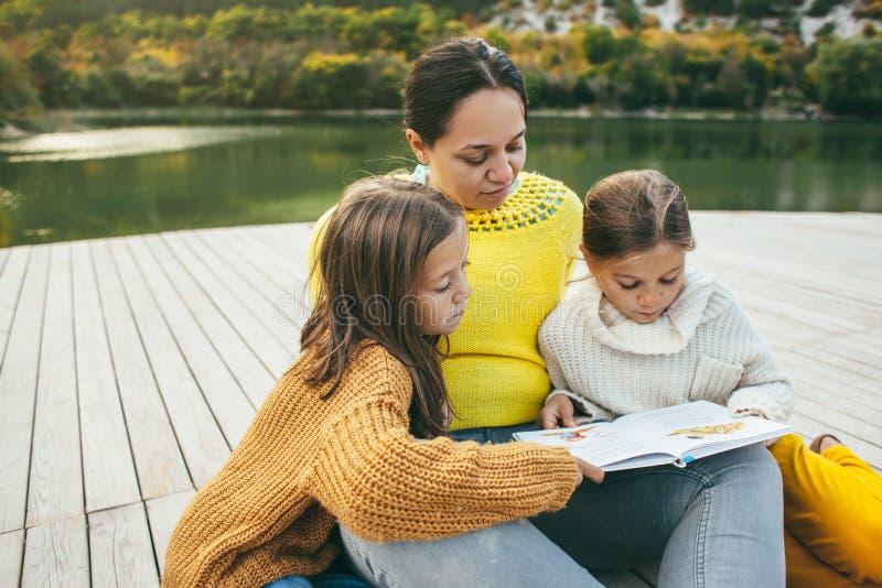 Familia que pasa el tiempo junto por el lago imagen de archivo