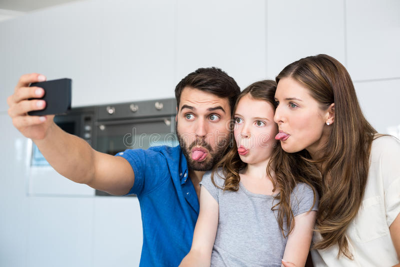 Familia que pega hacia fuera la lengua mientras que hace clic el selfie imagen de archivo