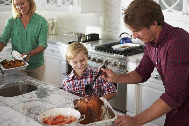 Familia que prepara la comida de Turquía de la carne asada en cocina junto foto de archivo