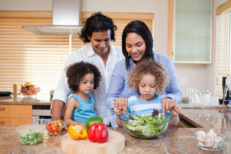 Familia que prepara la ensalada junta en la cocina fotos de archivo libres de regalías