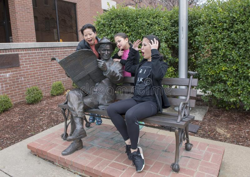 Familia que presenta chistoso con el bronce de la voluntad Rogers en un banco, Claremore, Oklahoma imagenes de archivo