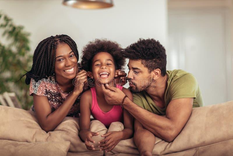 Familia que presenta en el sofá junto en casa en la sala de estar fotos de archivo