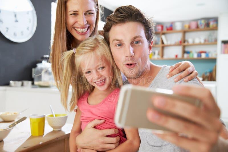 Familia que presenta para Selfie en la mesa de desayuno fotografía de archivo libre de regalías