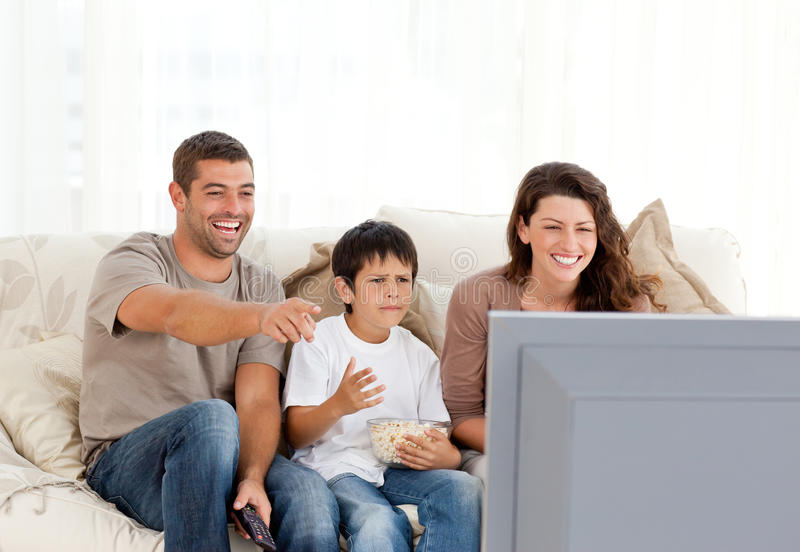 Familia que ríe mientras que mira la televisión junto fotos de archivo libres de regalías