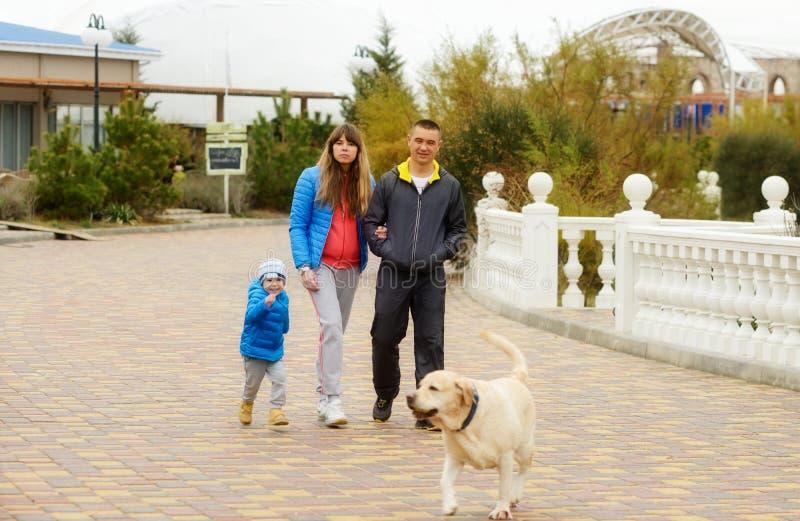 Familia que recorre con el perro imagen de archivo