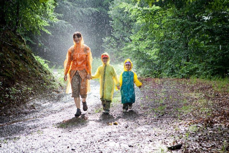 Familia que recorre en la lluvia imagenes de archivo