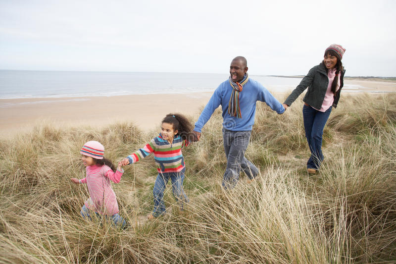 Familia que recorre a lo largo de las dunas en la playa del invierno fotos de archivo