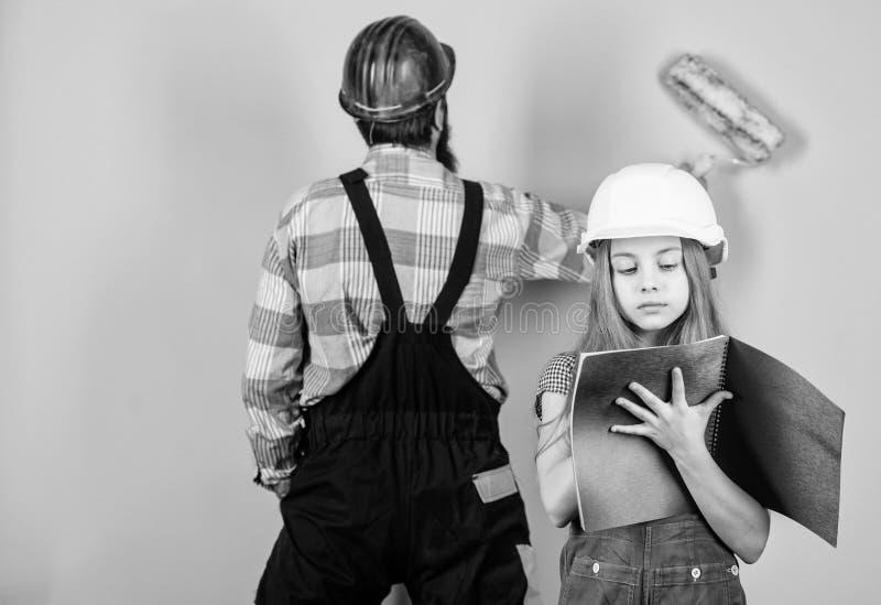 Familia que remodela la casa Poco engendra al ayudante Uniforme barbudo del casco del casco del hombre y de la hija del padre que imagen de archivo