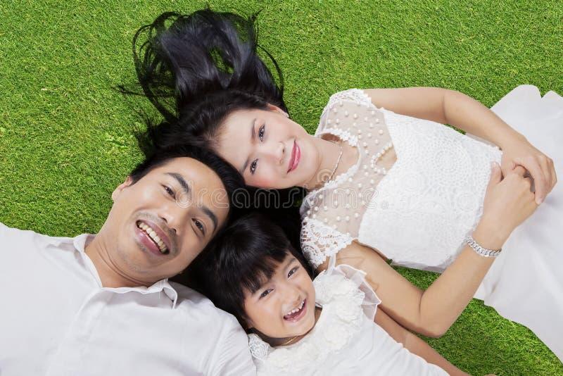 Familia que se acuesta en hierba verde fotografía de archivo libre de regalías