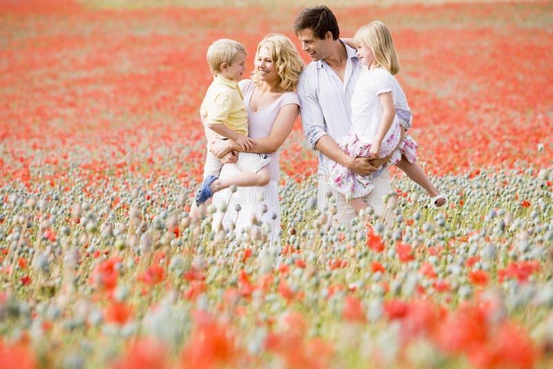 Familia que se coloca en la sonrisa del campo de la amapola foto de archivo libre de regalías