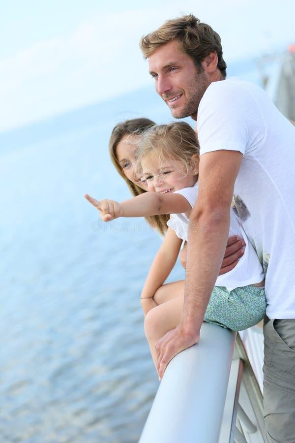 Familia que se coloca en un pontón que mira el mar imagen de archivo