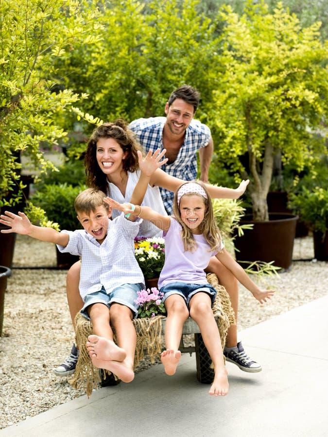 Familia que se divierte con una carretilla en un invernadero imagenes de archivo