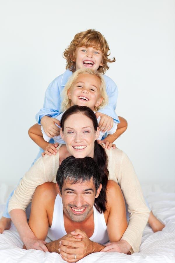 Familia que se divierte en cama imagenes de archivo