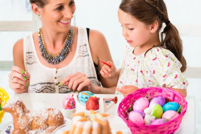 Familia que se divierte que colorea los huevos de Pascua imagen de archivo
