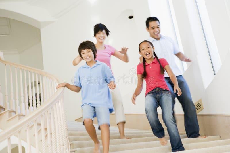 Familia que se ejecuta abajo de la sonrisa de la escalera fotos de archivo