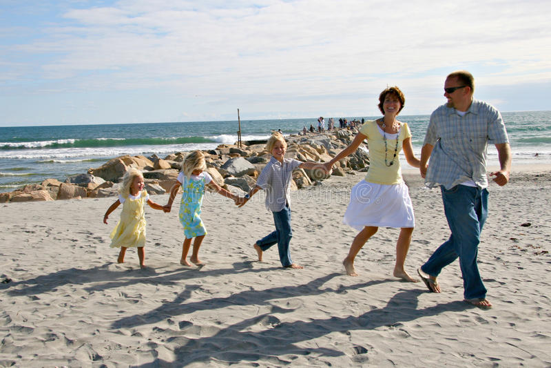 Familia que se ejecuta en la playa