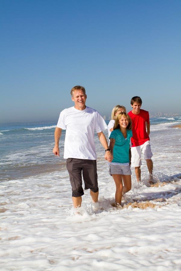 Familia que se ejecuta en la playa imagen de archivo