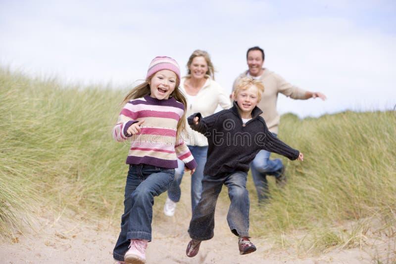 Familia que se ejecuta en la sonrisa de la playa fotos de archivo