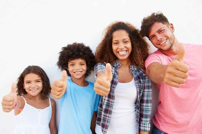 Familia que se opone al aire libre a la pared blanca que da los pulgares para arriba imagen de archivo libre de regalías
