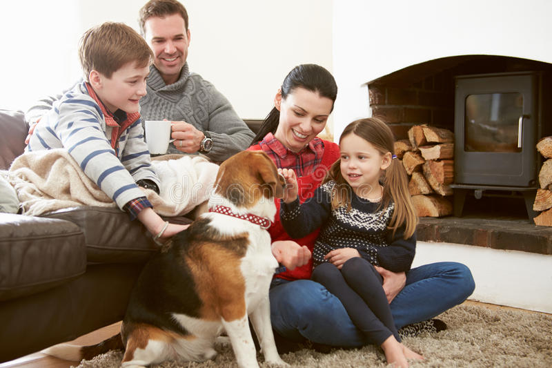 Familia que se relaja dentro y que frota ligeramente el perro casero fotografía de archivo libre de regalías