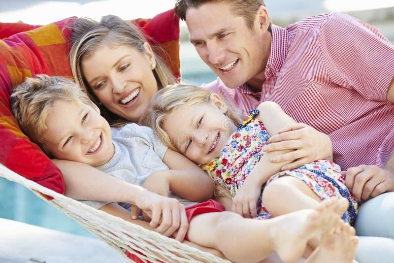 Familia que se relaja en hamaca del jardín junto imagen de archivo