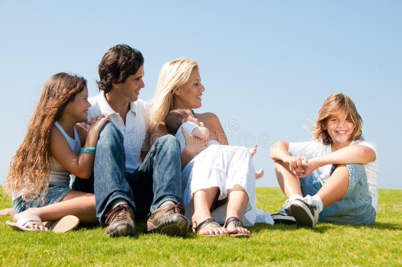 Familia que se relaja en hierba fotografía de archivo libre de regalías