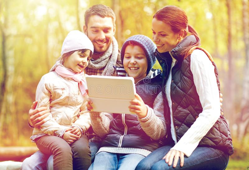 Familia que se sienta en banco con PC de la tableta en el campo imagenes de archivo