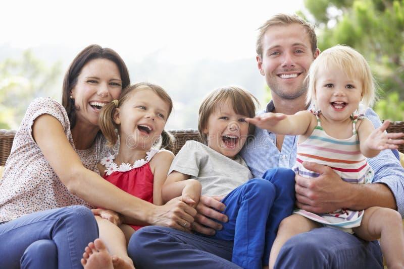 Familia que se sienta en el jardín Seat junto fotos de archivo libres de regalías