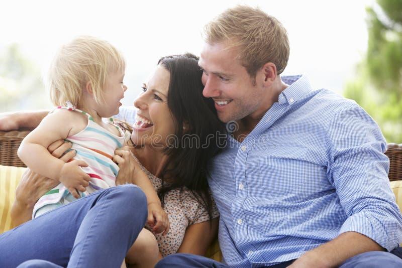 Familia que se sienta en el jardín Seat junto imagenes de archivo