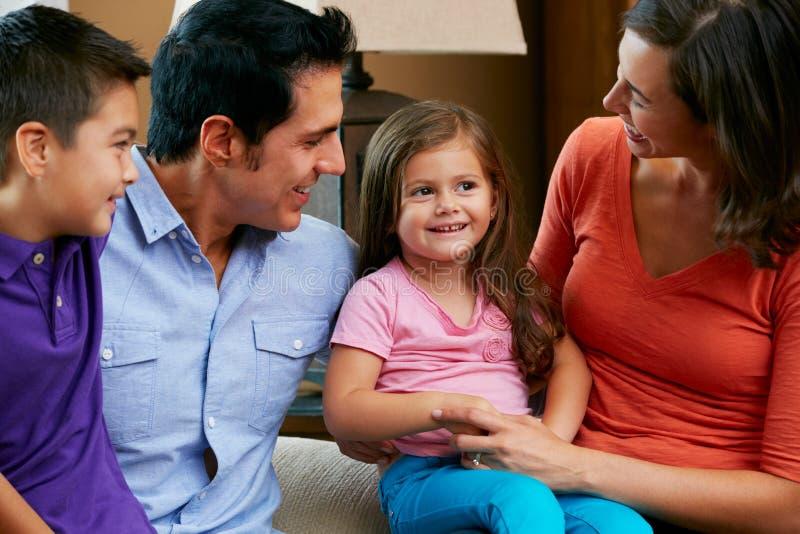 Familia que se sienta en el sofá en casa junto fotografía de archivo libre de regalías