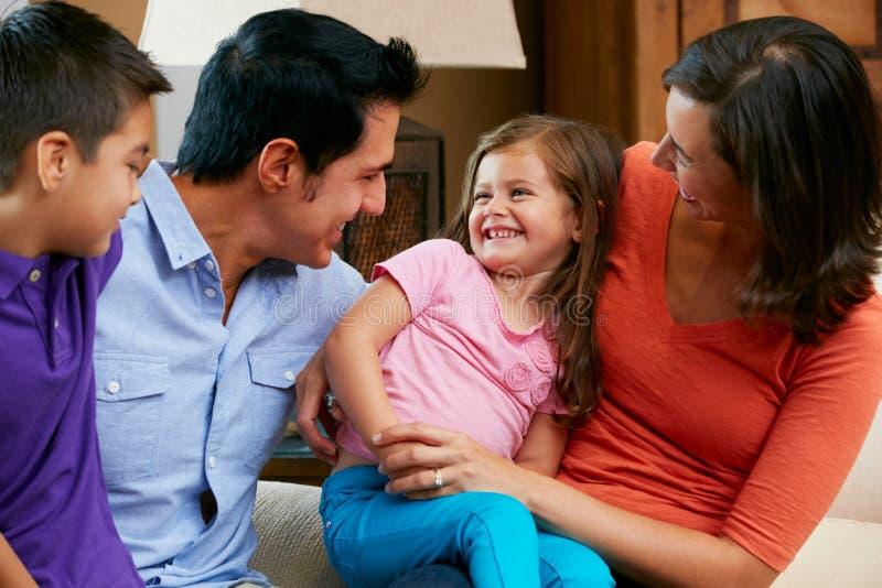 Familia que se sienta en el sofá en casa junto foto de archivo libre de regalías