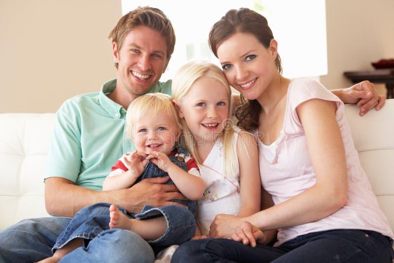 Familia que se sienta en el sofá en el país junto fotografía de archivo libre de regalías