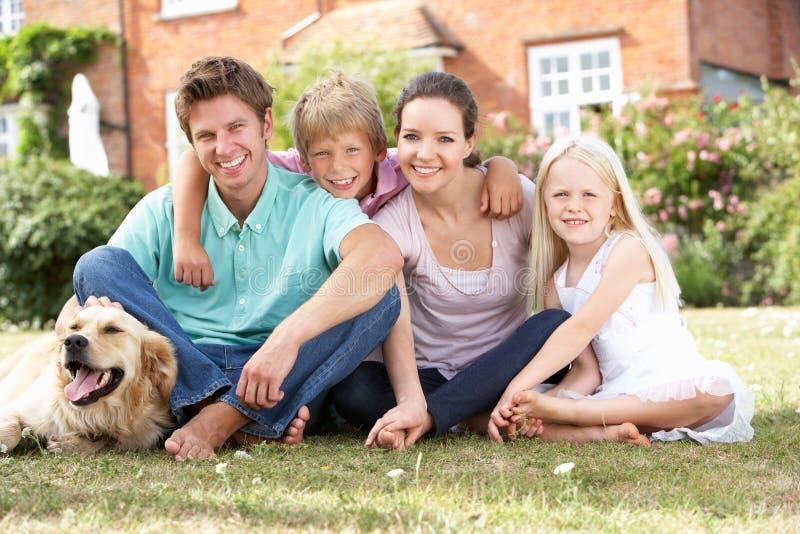 Familia que se sienta en jardín junto fotografía de archivo libre de regalías