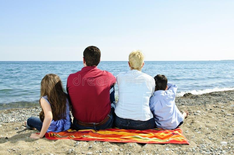 Familia que se sienta en la playa foto de archivo libre de regalías